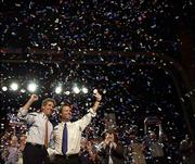 In a blitz of confetti, Democratic presidential candidate Sen. John Kerry, D-Mass., left, and his newly selected running mate, Sen. John Edwards, D-N.C., acknowledge the crowd during a campaign rally in Tampa, Fla. Wednesday was the first full day of campaigning for the pair.