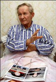 Charles Robert Jenkins, the husband of Hitomi Soga, one of five Japanese citizens abducted to North Korea and later freed in Japan, talks to Kyodo News, beside his family photos, in this Nov. 29, 2002, file photo at a Pyongyang hospital, where he was treated for extreme fatigue. Jenkins and his two daughters living in North Korea will fly Friday to Jakarta, Indonesia, to meet his wife.