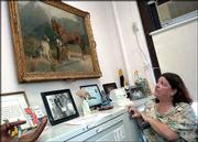 "Robyn Sims, president of the Woodrow Wilson Middle School Home and School Board, looks over an 1891 Henry Tanner painting, ""Horse and Dogs in a Landscape,"" that hangs in Principal James McWilliams office. The school district has uncovered millions of dollars worth of art in school basements, boiler rooms and hallways."