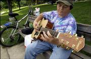 "Robert Taylor sings and plays some songs of inspiration on his guitar in Buford M. Watson Jr. Park. ""I thought it was gonna rain,"" Taylor said as he sat playing his six-string Thursday."