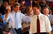 "As vice presidential candidate Sen. John Edwards D-N.C. is introduced to the crowd, presidential candidate Sen. John Kerry, D-Mass., gestures ""John 2"" for his running mate, during a campaign stop Thursday in Fort Lauderdale, Fla."