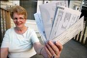 Dale Gravelle holds up some of the credit card statements that she still owes money on after running up more than $22,500 in debt. Despite paying her mortgage and car payments on time, Gravelle managed to run up her credit card debt. Gravelle, pictured July 1 at her home in Attleboro, Mass., is now paying them off using a debt consolidation company.