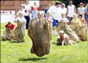 Charley Carver, 6, of Ozawkie, leads the pack in the gunny sack race during the Old Settlers Reunion in Oskaloosa. Games, crafts and carnival rides were the norm during Saturday's events at the downtown square.