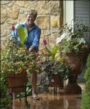 Mary Olson maintains flowers and plants in her numerous pots and containers. Olson keeps several of the container gardens on her patio outside the front door of her home.