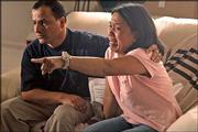 Lydia de la Cruz Ghazzawi, right, and her husband, Khaled Ghazzawi, watch the Philippine News at their home in Pacifica, Calif., as her brother, Angelo De la Cruz, was shown Friday. The Philippines confirmed Saturday it would withdraw its small peacekeeping contingent from Iraq on July 20, as planned, but it was unclear if the announcement had saved the life of De la Cruz, a Filipino hostage being held in Iraq.