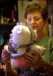 Barbara Usher examines a doll to see if it is in good enough condition to donate for children at the Emergency Aid-Food Bank in Salina.