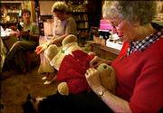 Neola O'Neal, right, sews up a stuffed teddy bear as Barbara Usher, left, and Evelyn O'Brien work on other dolls during a gathering in Salina.