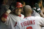 Anaheim Angels' Bengie Molina, left, celebrates after scoring on his grand slam against the Toronto Blue Jays with teammate Chone Figgins during the seventh inning. The Angels beat the Blue Jays, 11-2, at Skydome on Saturday in Toronto.