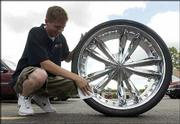 "Tyler Bradney, 19, an employee at Wendland Performance Motorsports Superstore, 2601 Iowa, cleans up a new 26-inch Jesse James soild aluminum rim with a low-profile tire. Big, shiny rims are becoming more popular as drivers begin to customize their vehicles a la MTV&squot;s ""Pimp My Ride."""