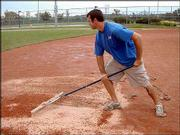 Matt Shroer, of Lawrence Parks and Recreation Facilities Maintenance II, rakes calcine clay into the infield at the Clinton Sports Complex after the rain July 9.