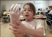 Sydney Combs, 5, puts on some gloves to keep from getting colored icing on her hands during an art project. Summer school started this week. Prairie Park School, where Sydney and other students are taking enrichment courses, such as language, art and drama, also offers the basics: math and reading.