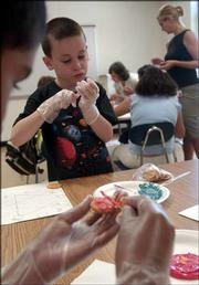 Nick Rice, 7, spreads two colors of frosting on a vanilla wafer to create a new color during an art class. Nick and his classmates were learned about the color wheel Tuesday. Sydney, Nick and their classsmates ate their completed work.