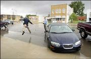 Something new in normally dry Johnson City: rain. Congressman Jerry Moran jumped the six-foot-stream of water running down the city's main street to get to his car. Garden City Telegram reporter Scott Aldis-Wilson watches the congressman in action.