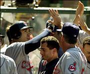 Cleveland's Travis Hafner, left, is congratulated by teammates after he hit his third home run of the day against Anaheim. Hafner, who also homered twice Monday, and the Indians beat the Angels, 14-5, Tuesday in Anaheim, Calif.