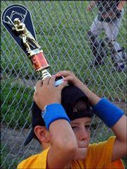 Ellyn Angelotti/World Online Photo Pirates player Kieran sets his first place trophy on his head during a postgame pep talk July 15. The Pirates beat the Sharks to win the postseason tournament and go undefeated for the season at 4-H fields.