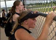 """Phenix players Natalie Reschke, front, and Theresa Harper watch a teammate hit against the K.C. Wild Things. The Phenix lost, 4-3, Thursday at the American Fastpitch Assn. """"B"""" Girls National Tournament on Thursday at Clinton Lake Softball Complex."""