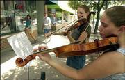 "Kansas University seniors Monica Mansholt, Shawnee, left, and Cori Simmons, Overland Park, perform duets on the sidewalk along the 700 block of Massachusetts Street. ""We think it&squot;s fun,"" said Mansholt, as the two played their instruments for passersby Thursday."