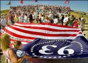 "Visitors to the memorial to United Flight 93 hold a ""hero flag"" in front of the memorial Sept. 7, 2002, at the Shanksville, Pa., crash site. The report from the Sept. 11 Commission portrays the heroism of the Flight 93 passengers as a defensive success amid the government&squot;s many failures."