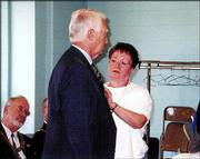 Master Mason Marion Manion, a member of Lawrence Masonic Lodge No. 6, receives his 50-year medal from his wife, Charlene. The award was pinned on him during ceremonies June 4 at the Holcom Recreation Center in Lawrence.