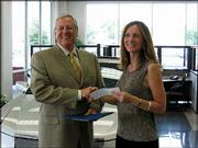 Dale Willey, chairman of Dale Willey Automotive, presents a $1,500 check to Susan Hazlett, executive director of the Lawrence Schools Foundation, for the Lawrence public schools' automotive vocational-technical program. He presented the check June 30 at the dealership, 2840 Iowa. Willey qualified for ambassador status with the National Automobile Dealers Charitable Foundation, enabling him to designate the donation, every three years, to the charity of his choice. Dale Willey Automotive and Lawrence High School are Lawrence Education Achievement Partners.