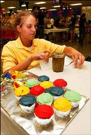Ashley Moran, 18, of the Eudora 4-H club, sorts through entry cards Monday afternoon at the Douglas County 4-H Fairgrounds. Moran entered her cupcakes in a food competition.