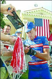 Lance Armstrong signs autographs before the start of the second stage of the Tour de Georgia in this file photo from April 21 in Thomaston, Ga. Armstrong won his record sixth straight Tour de France on Sunday.