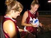 "18-U Phenix players Jacqueline Pyle and Laura Drivetta open picture frames given to them by by players from the Dakota Wild after an 11-1 loss in the opening round of pool play at the American Fastpitch Assn. Naitonal ""B"" Tournament game July 19 at Clinton Lake Sports Complex. All of the teams exchanged gifts representing something about their team with their first opponent."