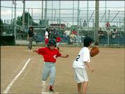Reds player Ryan Gleue makes it it to first base safely while Nat Caron covers the bag during a Jhawk Baseball League game against the Red Sox July 22 at Holcom. The Reds won the game 13-7.