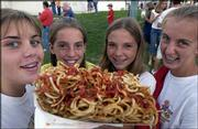 From left, Hannah Elder, 13, Mackenzie Flory, 12, Kelly Baker, 13, and Tracie Weege, 13, all of Baldwin, enjoy their enormous order of curly fries at the Douglas County Free Fair Friday. Large portions are a county fair staple.