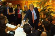 "Donald Trump greets potential candidates for ""The Apprentice"" TV reality show during the first day of auditions for next season. Hundreds lined up Friday in New York to get a shot at being on the show."