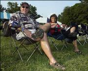 Dick Wise and Melissa Murphy listen to some live music during The Big Pig, a fund-raiser for the Boys & Girls Club of Lawrence. The event, which featured all-you-can-eat barbecue, was July 17 at the Meadowbrook apartment complex in Lawrence.