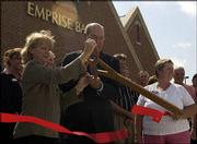 Cindy Yulich and Dave Adams, of Emprise Bank, cut a ribbon at a ceremony marking the opening of the bank's new area headquarters at 1121 Wakarusa Drive. The bank celebrated the opening of its new location with a ribbon-cutting ceremony and reception on July 16.