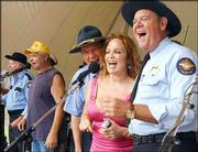 Dukes of Hazzard cast members, from left, Sonny Shroyer as Deputy Enos Strate, Catherine Bach as Daisy Duke, and Rick Hurst as Deputy Cletus Hogg, sing to the show's theme song during the 25th Anniversary DukesFest Saturday, in Bristol, Tenn.