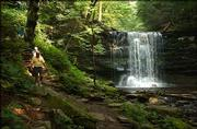 Reinhold Krick leads his sister, Mary Krick, along the Falls Trail past the 27-foot Harrison Wright Waterfall in Ricketts Glen State Park. A confluence of creeks running down the Allegheny Front Trail make for almost two dozen waterfalls at Ricketts Glen.