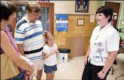 New York School Principal Nancy DeGarmo, right, talks with Christine and Vance White about their daughter Caroline, 6, an incoming first-grader, during enrollment. Caroline enrolled on Wednesday. DeGarmo is one of three new principals this year in the Lawrence school district.