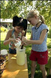 Chloe Sotomayor 7, and Lily Allen 7, both of Lawrence, mix up lemonade at Allen's home in the 900 block of West Fourth Street. The girls hoped Tuesday's sweltering temperatures would bring business to their stand.