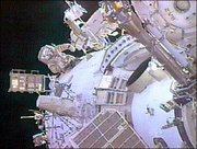Expedition 9 Commander Gennady Padalka, facing camera on left, works on the exterior of the Zvezda module during a televised spacewalk. Padalka and astronaut Mike Fincke, on right with back to camera, installed reflectors and communications equipment on the exterior of the International Space Station on Tuesday.