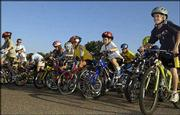 The children's race begins at the Cycle Works Twilight Bicycle Race, where interest has been spurred by Lance Armstrong's recent string of victories at the Tour de France. The young cyclists raced at the final event in this summer's series Thursday at Haskell Indian Nations University.