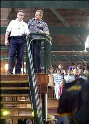 August 2004: Lawrence Police Chief Ron Olin, left, and an unidentified police officer watch over the crowd at Abe & Jake's Landing, 8 E. Sixth St. Olin said police were joined by Douglas County Sheriff's officers, Kansas Highway Patrol and the Kansas University Public Safety Office in providing security for Democratic vice presidential candidate John Edwards' Lawrence visit.