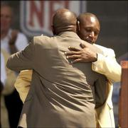 Barry Sanders, right, hugs his father, William, before speaking at the Pro Football Hall of Fame. Barry Sanders was inducted Sunday in Canton, Ohio.