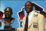 Barry Sanders stands with his bust after his induction into the Pro Football Hall of Fame. The former Detroit Lion was one of four players honored Sunday at Canton, Ohio.