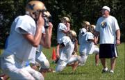 Veritas Christian football coach Doug Bennett, right, leads his players through drills during the first day of practice. The Eagles worked out Monday at Community Bible Church.