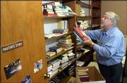 THE REV. BILL WOODARD UnPACKS BOXES of books and papers in his new office at West Side Presbyterian Church, 1024 Kasold Drive. Woodard is the new full-time pastor at the church, which had interims serve for two years.
