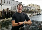 """Trevor Corson, author of """"The Secret Life of Lobsters: How Fishermen and Scientists are Unraveling the Mysteries of our Favorite Crustacean,"""" poses along the waterfront in Portland, Maine. Corson spent two years working on a lobster boat in the Gulf of Maine as part of his research for the book."""