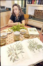 Carol Huettner displays a book featuring antique drawings of herbs such as basil, a key ingredient of pesto sauce. She was pictured Friday at her home in North Lawrence. Huettner makes pesto using basil from her garden.