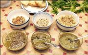 Pesto is traditionally prepared by using basil, although some cooks use cilantro, arugula or even mint. Other basic ingredients include olive oil, Parmesan cheese, garlic and nuts. These bowls of pesto were made using the basic ingredients and, from left, pecans, hazel nuts and walnuts.