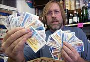 Jeff Jensen, owner of Jensen Liquor, 620 W. Ninth, gets a rush of customers using fake ID's this time of year. Thursday he displayed about 40 of the bogus ID's confiscated at his store since the beginning of July.