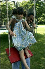 Paulina Cooper, 6, is helped into a swing by her father, James. Paulina has an inoperable brain tumor and travels monthly to Chicago with her mother to receive experimental treatments. Paulina and her father played Wednesday.