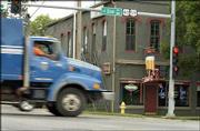 """A truck approaches the """"bump"""" in front of Johnny&squot;s Tavern in North Lawrence, a road hazard that some claim has been there since the late 1960s. While city officials say the dip actually is only about a decade old, they agree it&squot;s been there long enough. The state has agreed to help pay for repairs at the intersection in the next few years."""