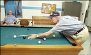Delbert Bradley, 76, of Lawrence, right, shoots pool at the Lawrence Senior Center with Don Heim 72. Bradley is one of many senior citizens who are concerned about the high cost of prescription drugs in the United States.